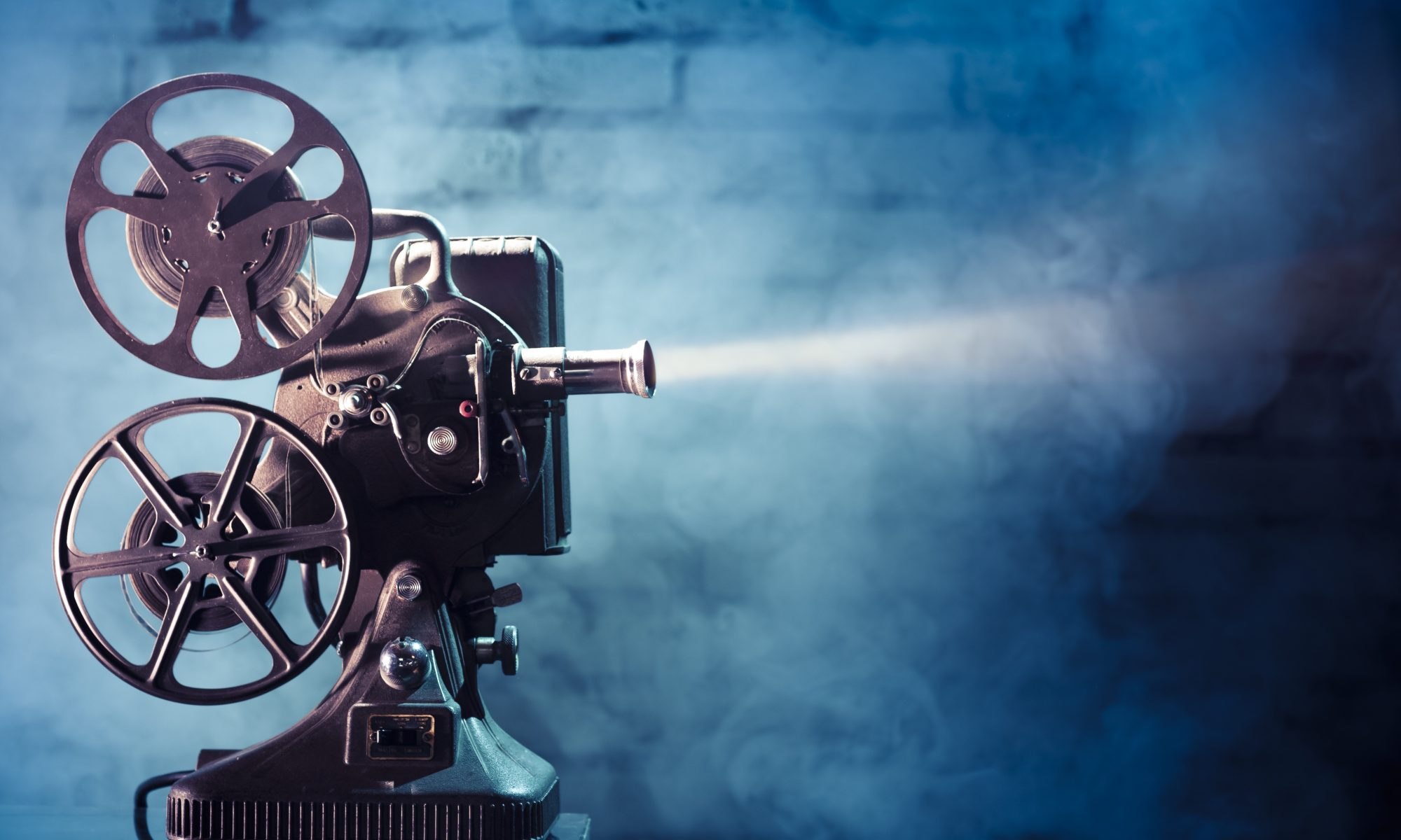 old fashioned film projector on blue background