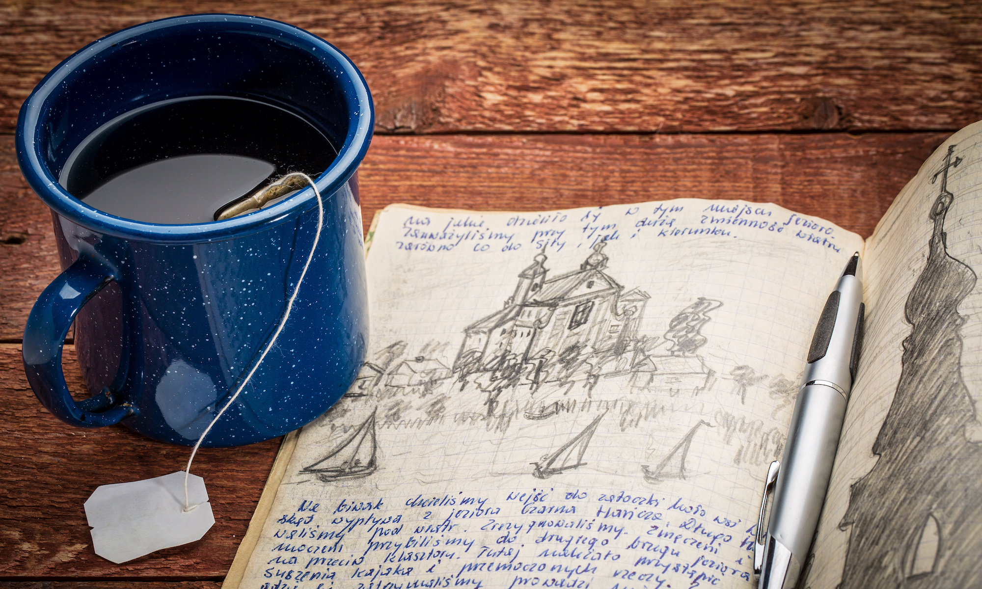 journal with handwriting and drawing in pencil in a notebook against rustic picnic table with cup of tea