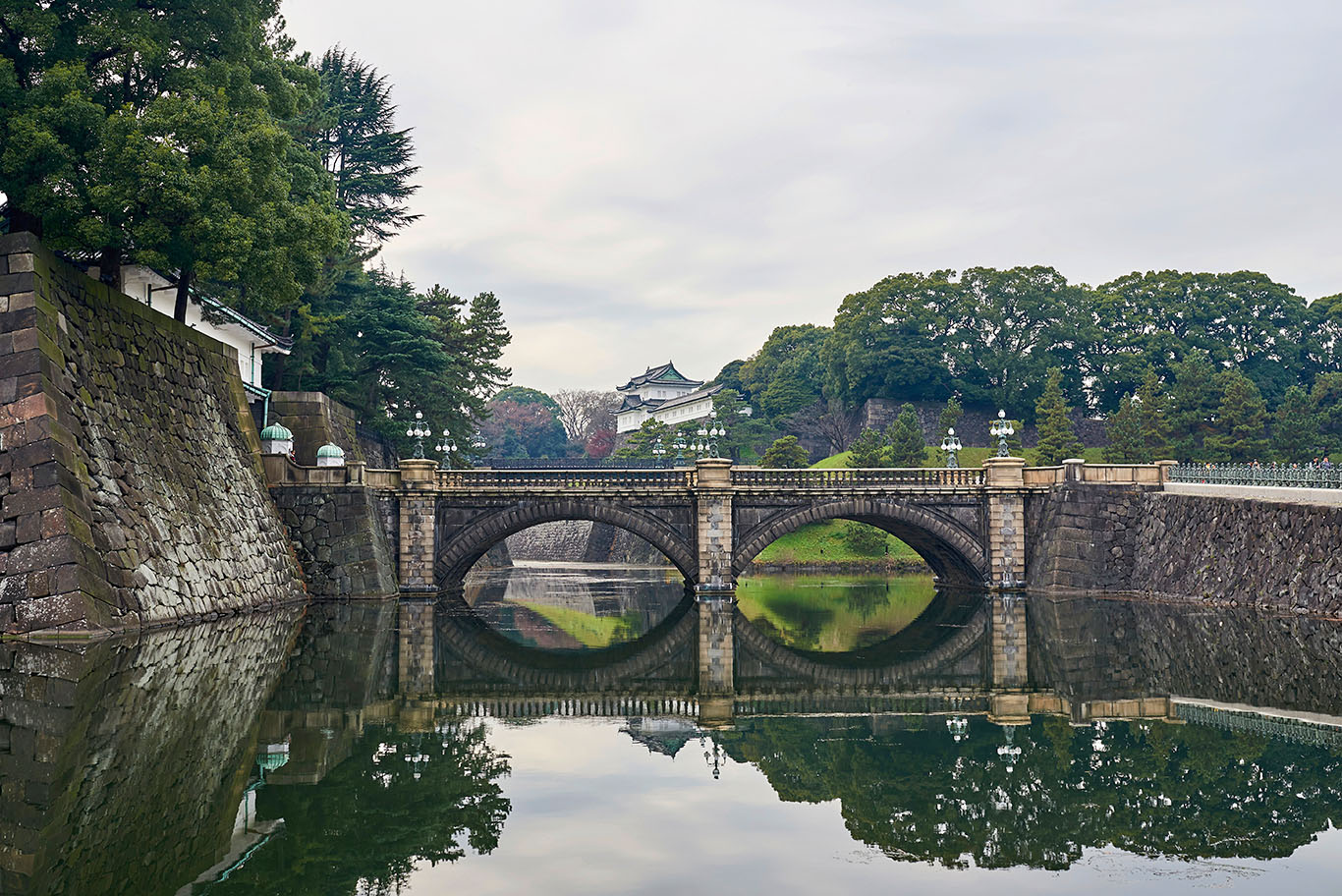 bridge over still water with Japanese-style buildings in distance