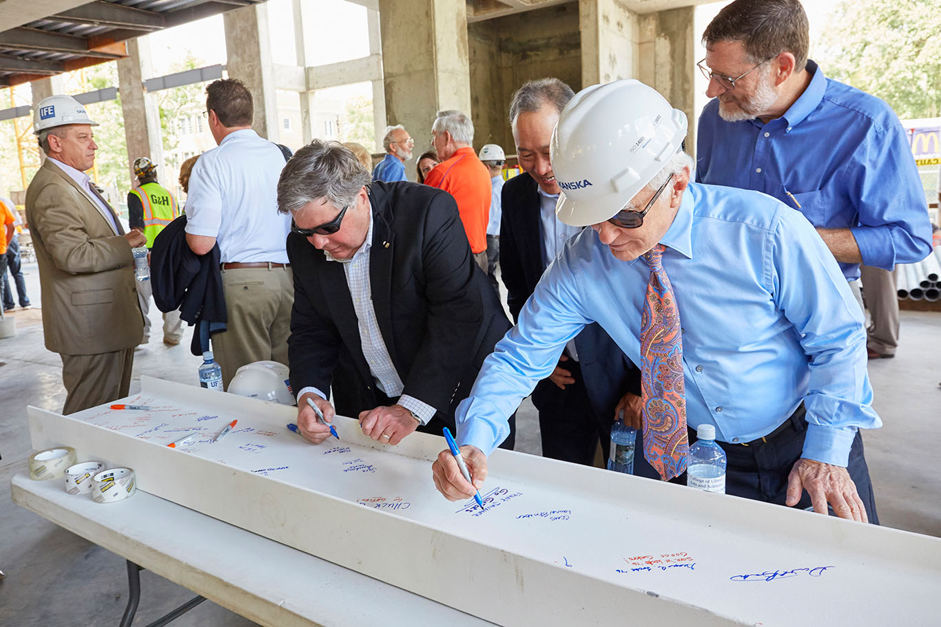 men wearing glasses and hard hats sign a beam