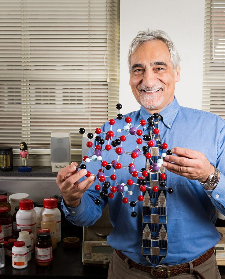 Photo of Professor Christou holding a molecule model.