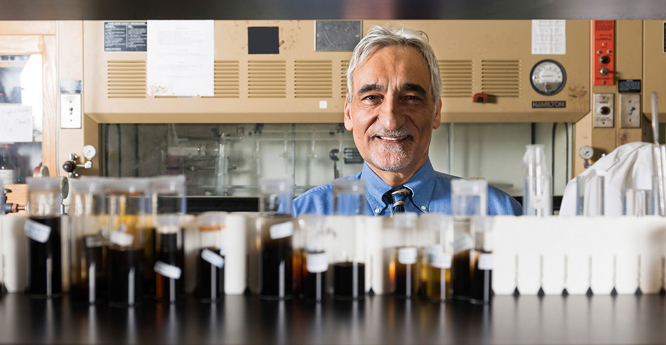 George Christou peers over row of vials