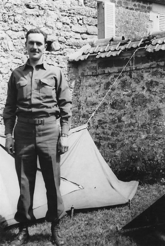 photo of Frank Towers standing in front of tarpaulin and stone wall