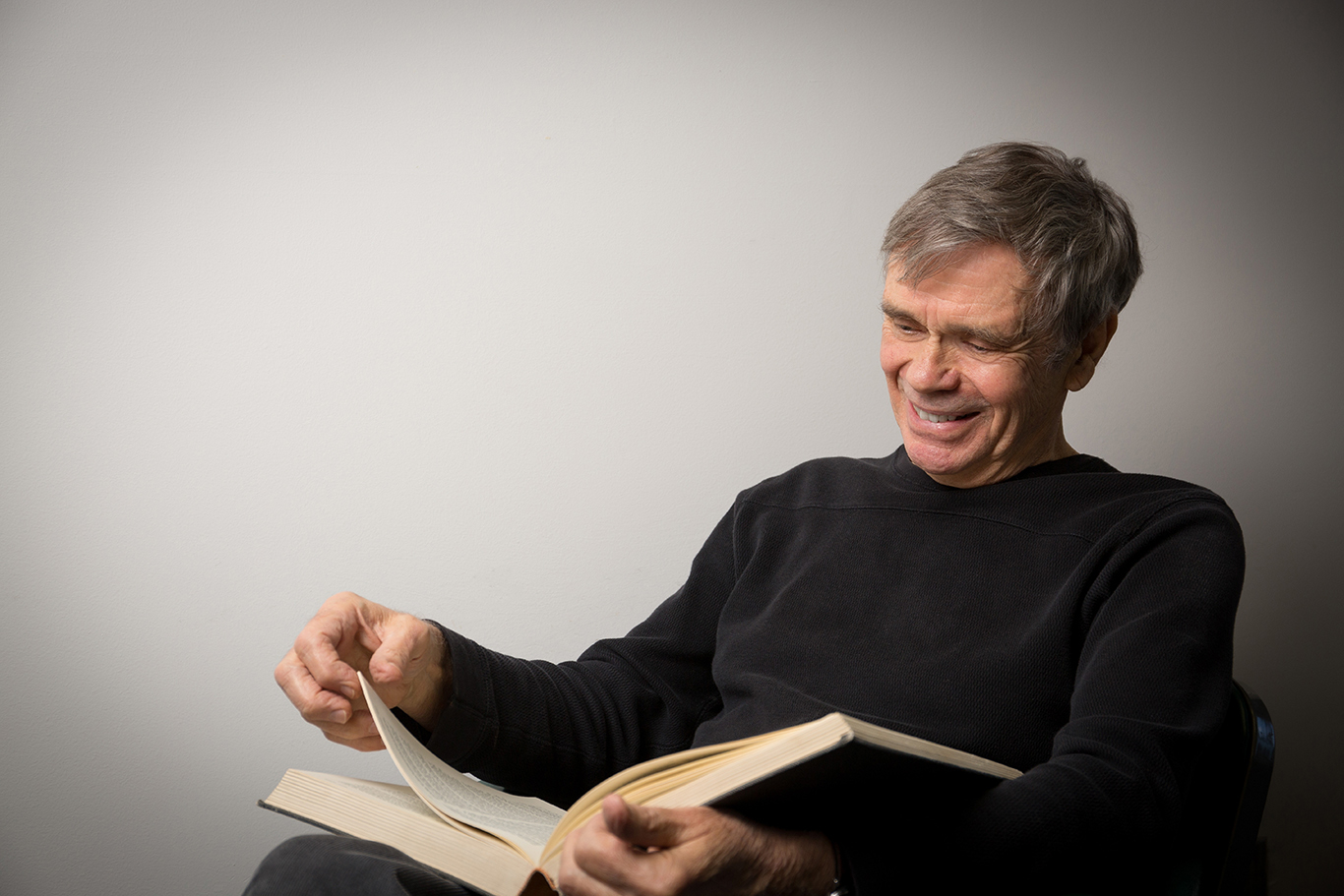 Photo of Professor Sid homan reading a book.