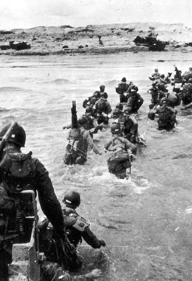 soldiers wade out of sea onto Normandy Beach