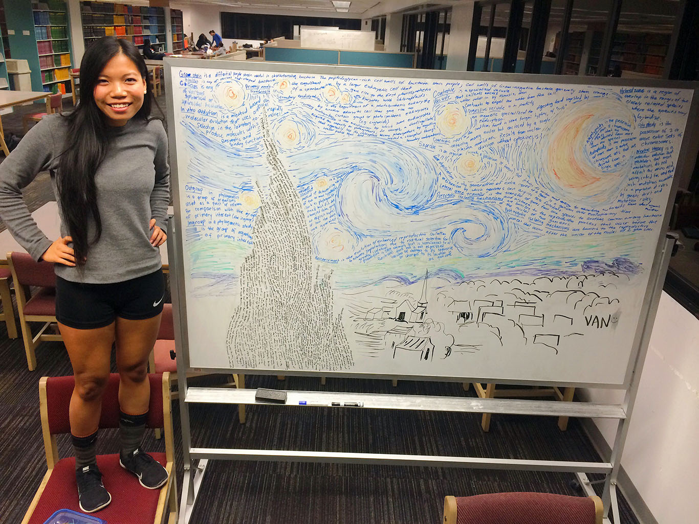 Van Truong standing next to her starry night artwork on a library whiteboard