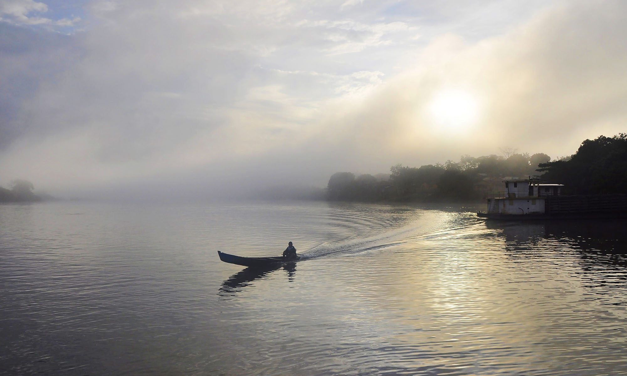 small boat on river with sunrise behind