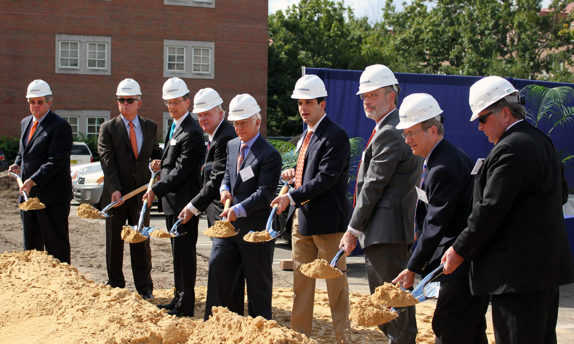A group of men hold shovels at the ceremonial groundbreaking