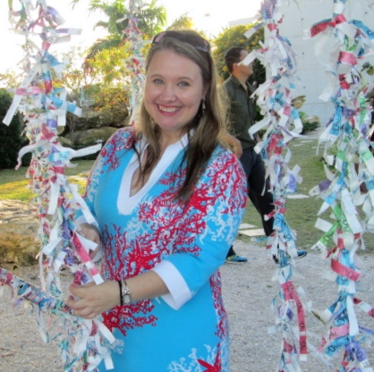 Jen stands among strands of woven colorful paper