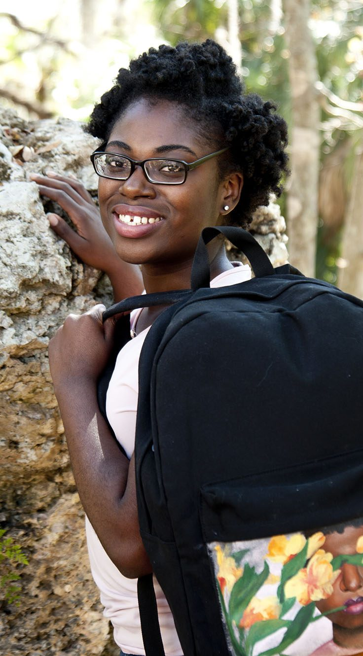 young woman holding backpack and leaning against boulder
