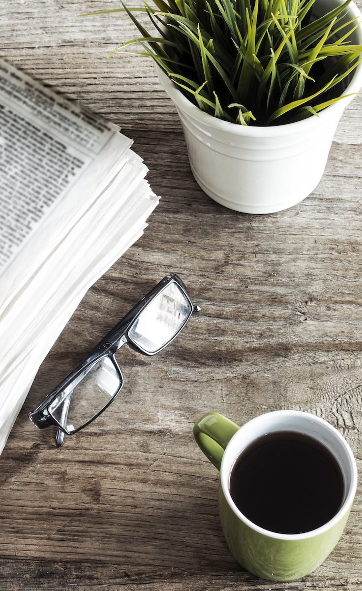 newspaper, plant, reading glasses, and coffee on wooden table