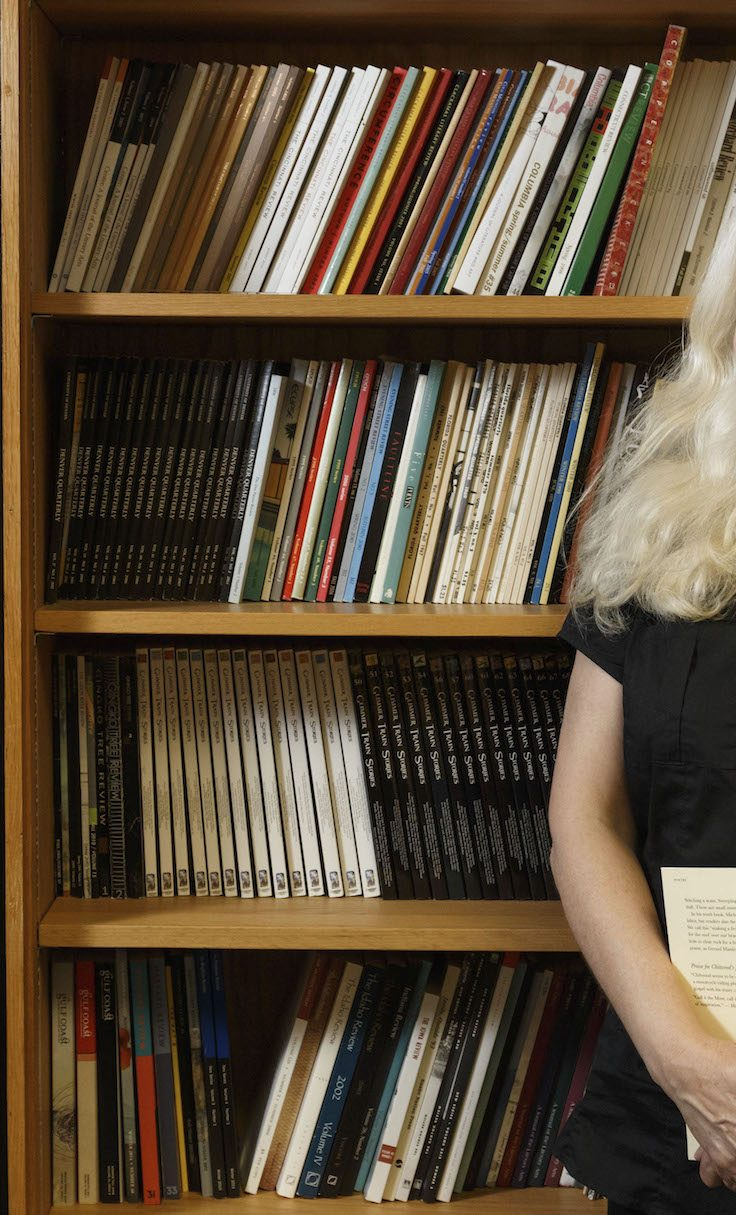 Amy Hempel stands in front of bookcase