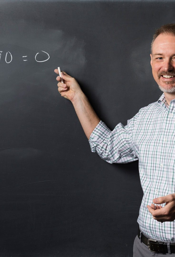 Kevin Knudson points to math equation written on chalkboard