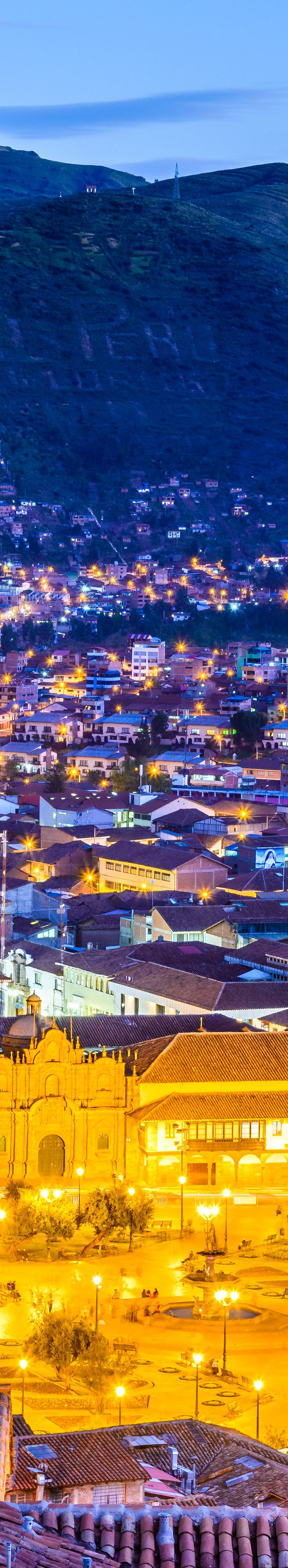 nighttime view of glowing city amidst mountains