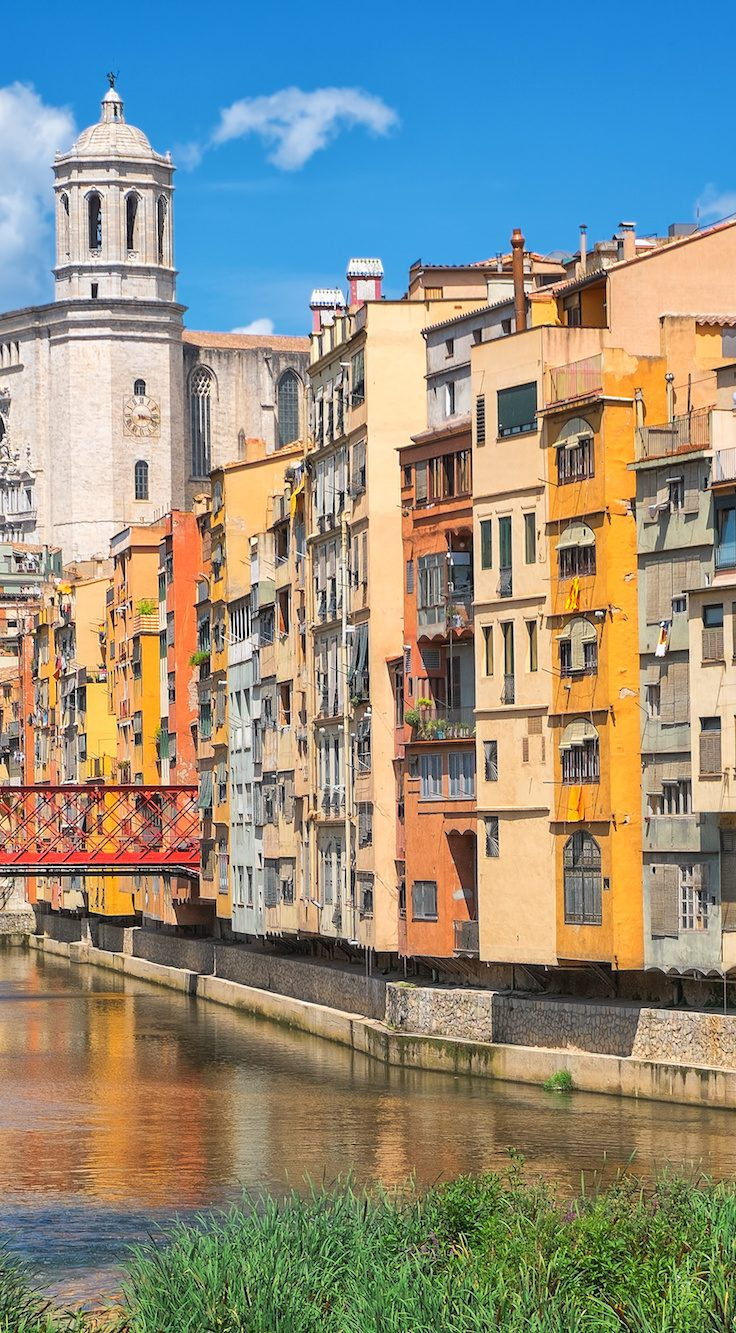 glowing cityscape of multi-colored buildings along river