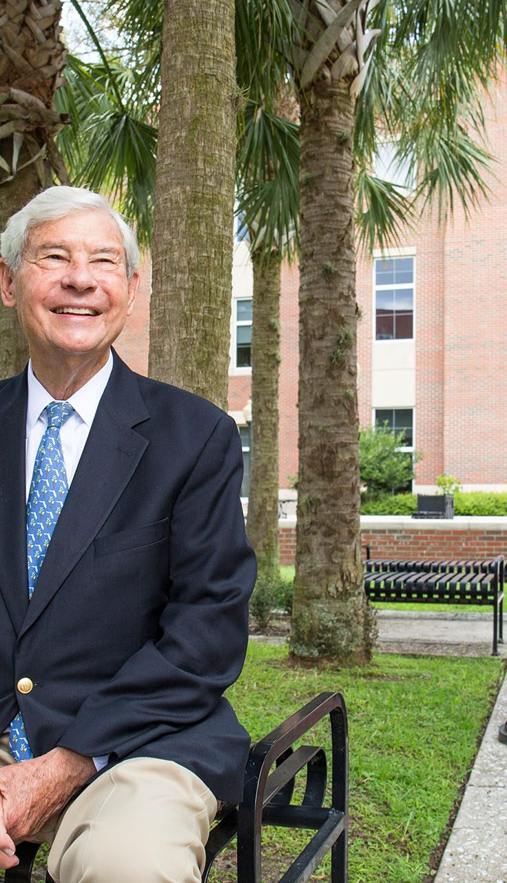 smiling grandfatherly man in suit sits on bench outside statuesque collegiate building
