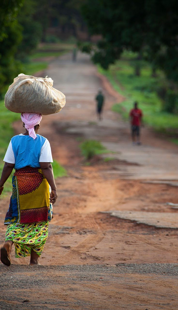 woman in traditional African garb walks down dirt road, a parcel balanced upon her head