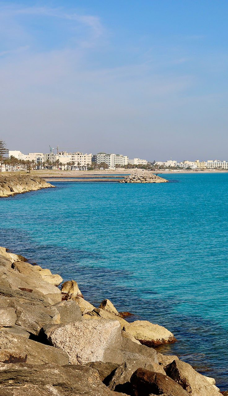 rocky shoreline with stunning blue waters, with cityline in background