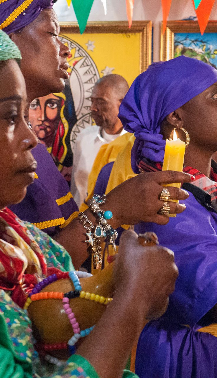 Haitian women adorned in vivid colors hold candles and instruments