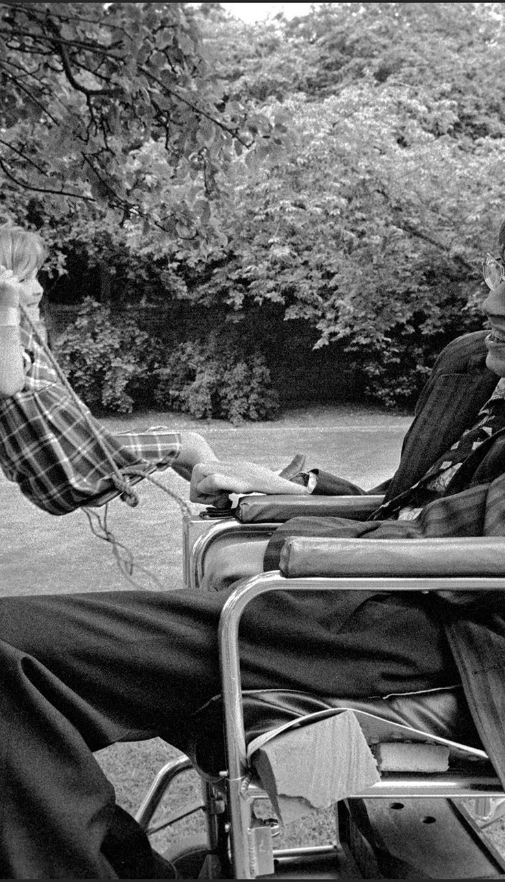 Stephen Hawking in chair as young girl swings on tree swing in background